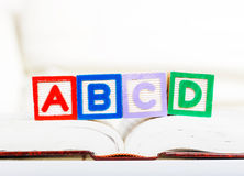 Alphabet block with ABCD on book Royalty Free Stock Photo
