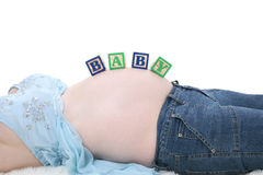 Alphabet Blocks Spell Baby Across Expecting Mom Belly royalty free stock image