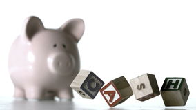 Alphabet blocks spelling cash dropping down in front of a piggy bank Stock Photos