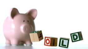 Alphabet blocks spelling sold dropping down beside a piggy bank Stock Photography