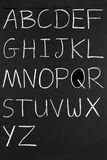 The alphabet in capitals. The alphabet in capitals written with white chalk on a blackboard stock photo