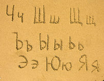 Alphabet (from Ch to Ja) written on a sand beach. Royalty Free Stock Images