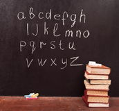 Alphabet on chalkboard. Alphabet on a chalkboard with books Stock Images