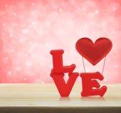 Alphabet d'amour et coeur rouges de tissu sur la table en bois au-dessus de la lumière pi Photos stock