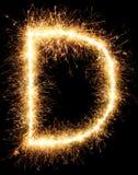 Alphabet D de lumière de feu d'artifice de cierge magique sur le noir Image stock