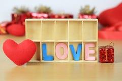 alphabet de l'AMOUR dans la boîte en bois près de la forme rouge et du boîte-cadeau de coeur Photos stock