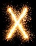 Alphabet X de lumière de feu d'artifice de cierge magique sur le noir Photo libre de droits