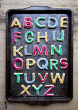 Alphabet in decorated colourful cookies on baking tray Royalty Free Stock Photo