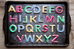 Alphabet in decorated colourful cookies on baking tray, horizontal Royalty Free Stock Photos