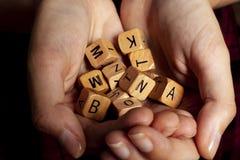 Alphabet dice in the hands. Dyslexia concept Stock Photos