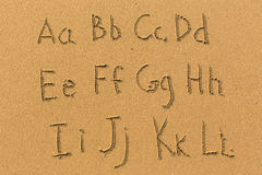 Alphabet drawn on the sand of a beach. Royalty Free Stock Photo