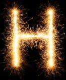 Alphabet H de lumière de feu d'artifice de cierge magique sur le noir Image stock