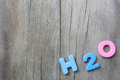 The Alphabet of H2O Lay on old brown wood floor background. The Alphabet of H2O Lay on old brown wood floor background and have copy space to your work design Stock Images
