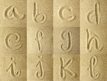 Alphabet handwritten in the sand. Golden colors Stock Photo