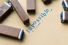 Alphabet letter word impossible from stamp letters font on paper Royalty Free Stock Image