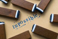 Alphabet letter word impossible from stamp letters font on paper Stock Photography