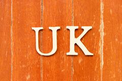 Alphabet in word UK (abbreviation of united kingdom) on old red color wood plate background