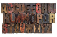Alphabet in letterpress wood type. English alphabet in lettterpress wood type printing blocks, stained by color inks Royalty Free Stock Photos