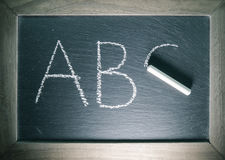 Alphabet letters abc written on chalkboard back to school concept with wooden frame Royalty Free Stock Images