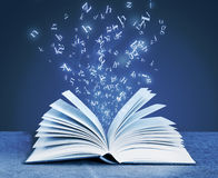 Alphabet letters around open book Royalty Free Stock Photo