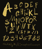 Alphabet letters lowercase, uppercase and numbers gold on black. Stock Photos
