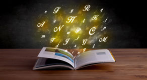 Alphabet letters over book Stock Photos