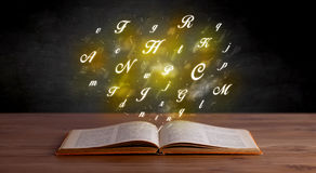 Alphabet letters over book Royalty Free Stock Photos
