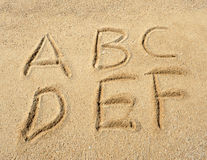 Alphabet letters in sand on beach Stock Images