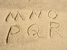 Alphabet letters in sand on beach Royalty Free Stock Photo