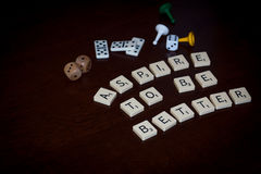 Alphabet letters spell out `ASPIRE TO BE BETTER` royalty free stock photography
