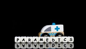 A toy ambulance and a word paramedics. Alphabet letters spelling a word paramedics with a model ambulance in the background. Medical emergency concept royalty free stock photo