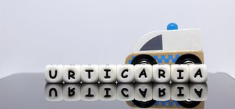 Alphabet letters spelling a word urticaria. A skin condition demands urgent medical treatment royalty free stock image