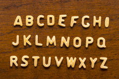 Alphabet made of macaroni letters isolated on wood background.  Stock Images