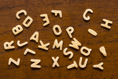 Alphabet made of macaroni letters isolated on wood background.  Royalty Free Stock Photo