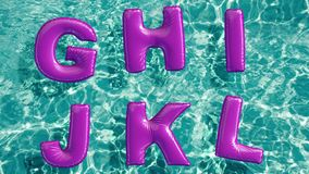 Alphabet made of shaped inflatable swim ring floating in a refreshing blue swimming pool stock video footage
