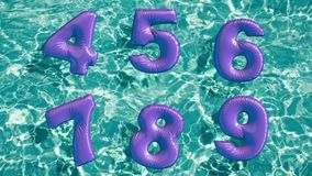 Alphabet made of shaped inflatable swim ring floating in a refreshing blue swimming pool Stock Images