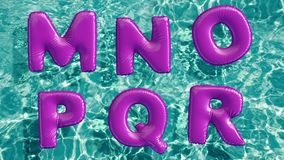 Alphabet made of shaped inflatable swim ring floating in a refreshing blue swimming pool stock video