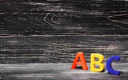 Alphabet made of wood on the background of a board, ebony. Royalty Free Stock Photos