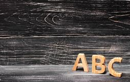 Alphabet made of wood on the background of a board, ebony. Royalty Free Stock Photography