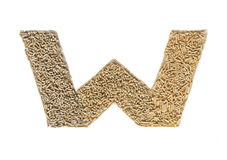 Alphabet made of wood pellets - letter W. Pelleted compound feed Isolated on white background Royalty Free Stock Photo