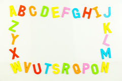 Alphabet magnets forming frame on whiteboard Stock Photos