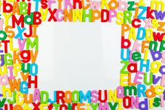 Alphabet magnets forming frame on whiteboard Royalty Free Stock Images