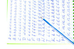 Alphabet in notebook into a cell. On top is the blue pen.  Isolate. Stock Image