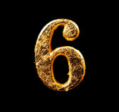 Alphabet and numbers in gold leaf. Isolated on black Stock Photos