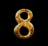 Alphabet and numbers in gold leaf. Isolated on black Stock Photo