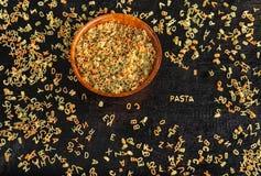 Alphabet pasta letters on black background stock photo