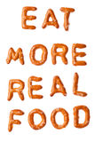 Alphabet pretzel slogan EAT MORE REAL FOOD isolated. Slogan words EAT MORE REAL FOOD written, laid-out, with crispy alphabet pretzels isolated on white Royalty Free Stock Photo