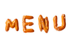 Alphabet pretzel written word MENU isolated. Word MENU written, laid-out, with crispy alphabet pretzels isolated on white background Royalty Free Stock Images