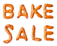 Alphabet pretzel written words BAKE SALE isolated Stock Photography