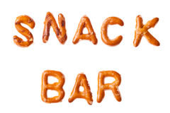 Alphabet pretzel written words SNACK BAR isolated. Word SALT written, laid-out, with crispy alphabet pretzels isolated on white background Stock Photos